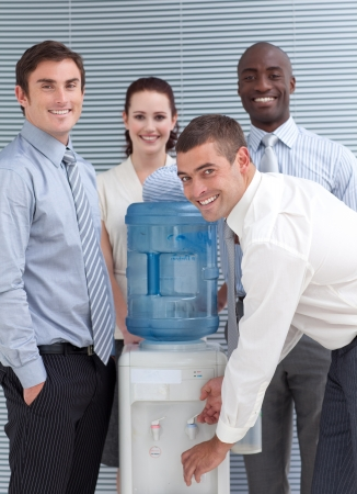 Busines people standing around water cooler in workplace photo