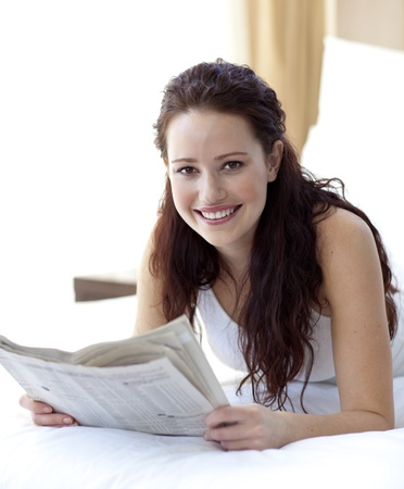 news paper: Beautiful woman in bed reading a newspaper