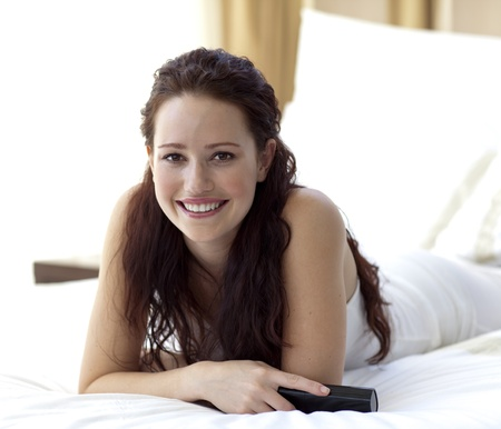 Beautiful woman in bed holding a remote control photo