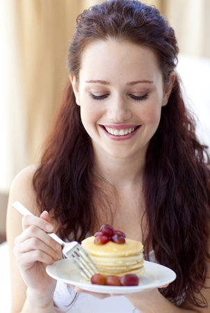 Smiling woman eating a sweet dessert photo