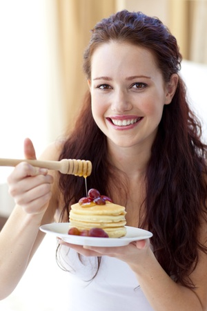 Smiling woman eating pancakes with fruit and honey photo