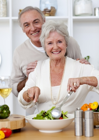 Felice coppia senior eeating una insalata in cucina
