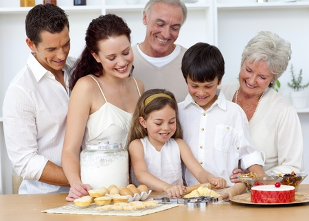 Parents and granparents looking at children baking photo