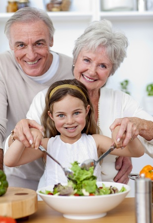 Smiling grandparents eating a salad with granddaughter photo