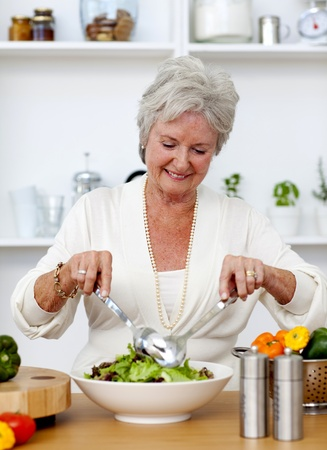 Happy senior woman cooking a salad photo