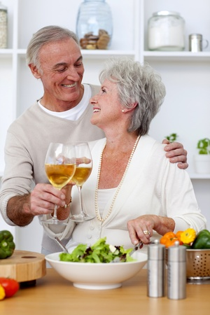 Senior couple in love eating a salad in the kitchen photo