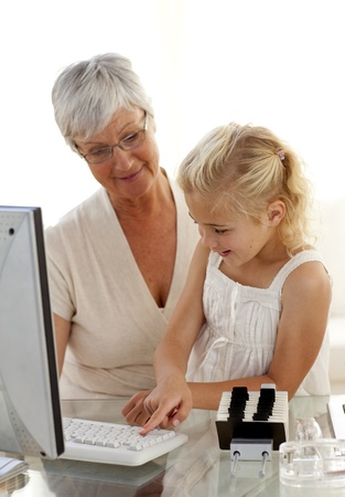 Granddaughter explaining her grandmother how to use a computer photo