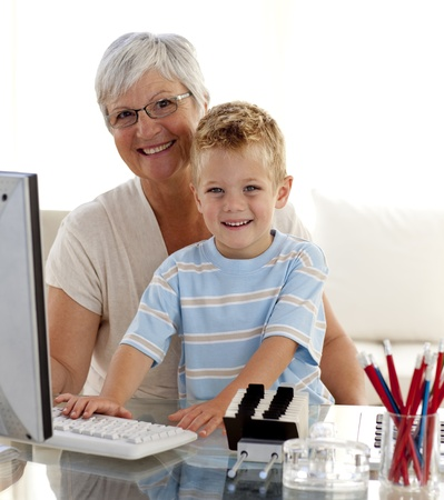 Happy grandson using a computer with his grandmother photo