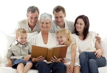 grandfather and grandmother: Grandmother reading a book to her family Stock Photo