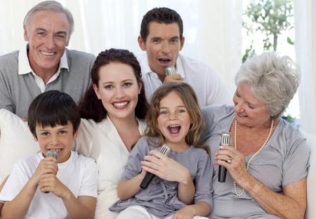 Family singing karaoke in living-room photo