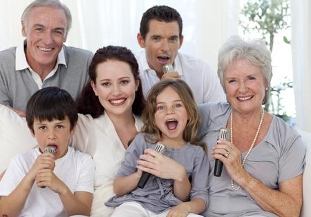 Happy family singing karaoke in living-room photo