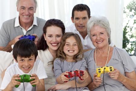 niños jugando videojuegos: Abuelos, padres e hijos jugando juegos de video