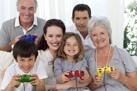 Grandparents, parents and children playing video games photo
