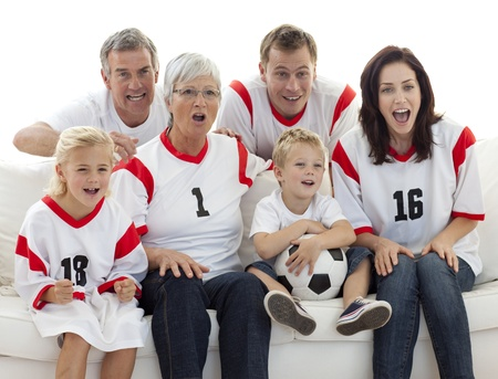 Excited family watching a football match in television photo