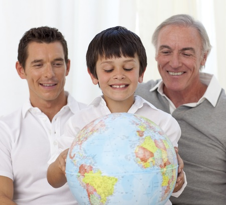 Son, father and grandfather looking at a terrestrial globe photo