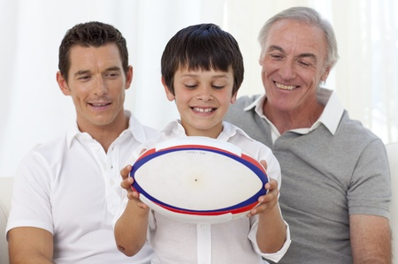 Son holding a rugby ball with his father and grandfather Stock Photo - 10256116