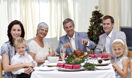 Family eating turkey in Christmas Eve Dinner photo