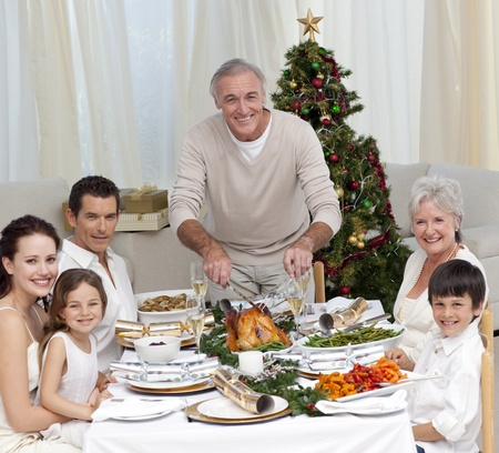 Grandfather cutting turkey for Christmas dinner photo