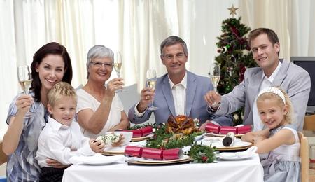 cena navide�a: Tusting familiar en una cena de Navidad con vino blanco Foto de archivo