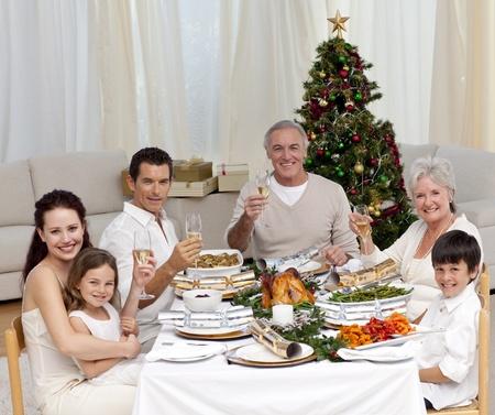 cena navide�a: Familia tusting con vino blanco en una cena de Navidad Foto de archivo