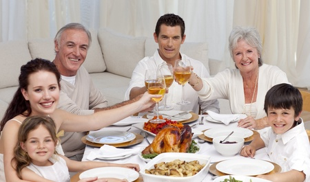 Happy family tusting with wine in a dinner photo