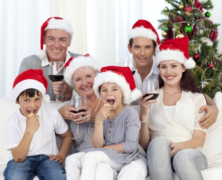 Family drinking wine and eating sweets in Christmas photo