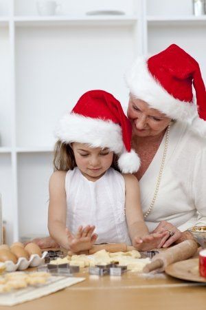 Grandmother and little girl baking Christmas cakes photo