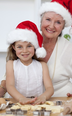 Smiling grandmother and little girl baking Christmas cakes photo