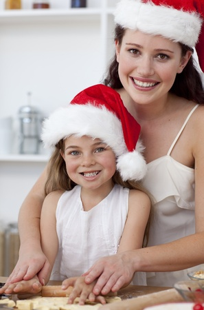 Smiling mother and daughter baking Christmas cakes photo