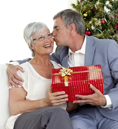 Senior man giving a kiss and a Christmas present to his wife photo