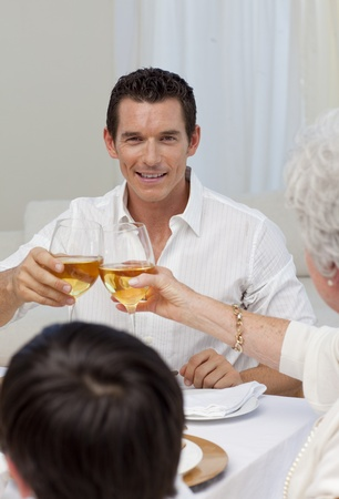 Attractive man toasting with his mother in a dinner photo