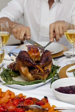 Close-up of a man cutting a turkey for Christmas dinner photo