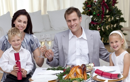 Parents toasting with wine in Christmas dinner photo