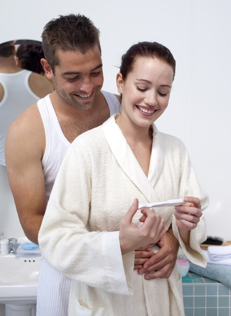 gestation: Happy couple in bathroom looking at pregnancy test Stock Photo