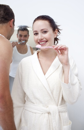 Woman and man cleaning their teeth in bathroom photo
