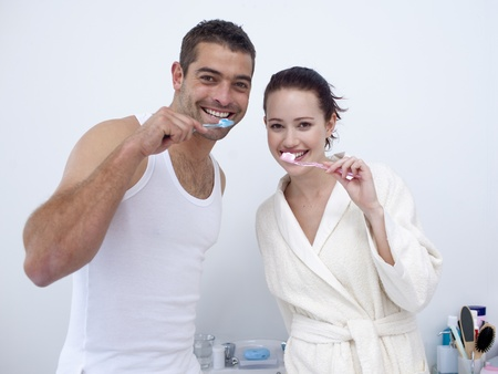 Couple cleaning their teeth in bathroom photo