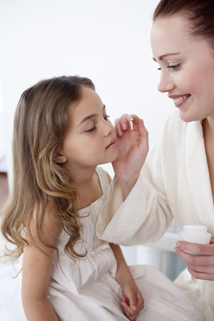 Mother putting cream on her daughters face photo