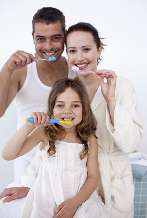 Family cleaning their teeth in bathroom photo