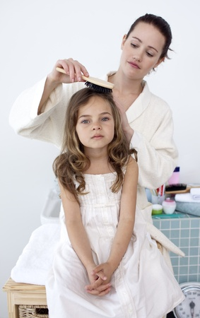 comb hair: Mother brushing her daughters hair