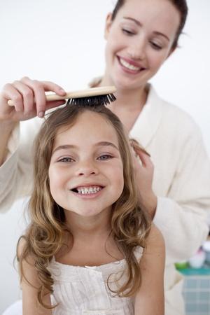 Retrato de madre haciendo el cabello de su hija Foto de archivo