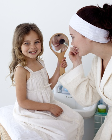 Mother applying blusher with her daughter photo