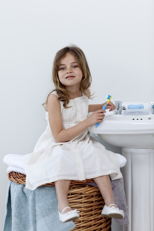 Little girl sitting in bathroom cleaning her teeth photo