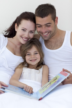 Parents and daughter reading in bed photo