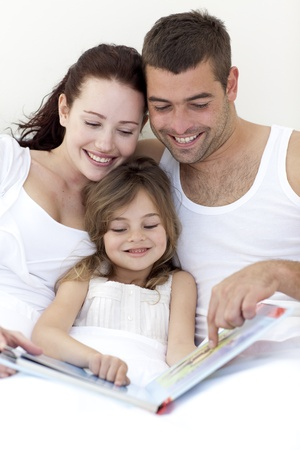 Young family reading in bed photo