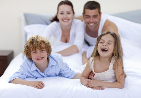 Brother and sister having fun in bed with their parents photo