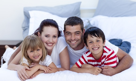 Family lying in bed together photo