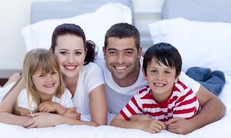 familia abrazo: Retrato de familia tumbado en la cama juntos Foto de archivo