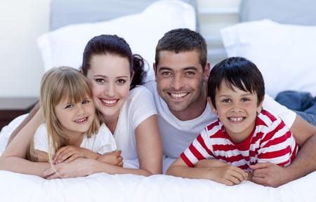 Sourire famille couché dans un lit