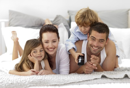 Family lying in bed watching television photo