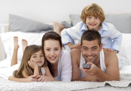 familia abrazo: Familia en la cama y el uso de un mando a distancia